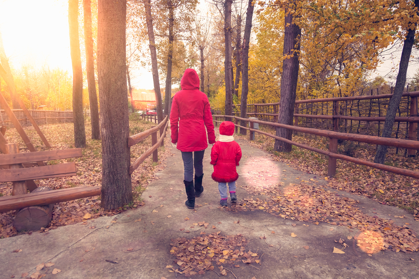 Small girl and woman go through the autumn park in red jackets. They turned their back and walk along the track with trees.